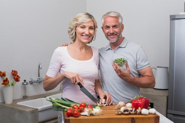 Gelukkig rijp paar die voedsel samen in keuken voorbereiden
