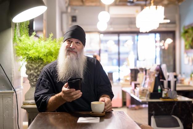 Gelukkig rijpe bebaarde hipster man denken tijdens het gebruik van telefoon in de coffeeshop