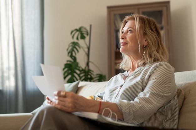 Gelukkig rijpe blonde vrouw in vrijetijdskleding denkend aan haar vrienden en familieleden terwijl ze door hun foto's kijkt terwijl ze thuis blijft