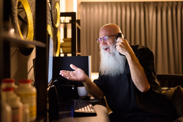 Gelukkig rijpe kale bebaarde man praten aan de telefoon terwijl hij 's avonds laat overuren thuis werkt