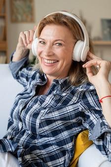 Gelukkig rijpe vrouw met brede glimlach, luisteren naar haar favoriete muziek in koptelefoon ontspannen in fauteuil