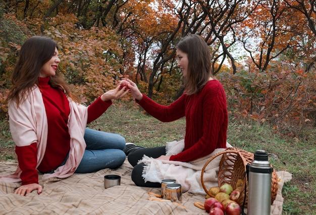 Gelukkig rijpe vrouw thee drinken met jonge dochter in bos op warme herfstdag. gezellige warme herfstdag, gezellige tijd met familie in de natuur