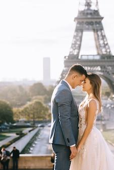 Gelukkig romantisch echtpaar knuffelen in de buurt van de eiffeltoren in parijs