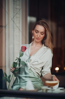 Gelukkig romantisch jong mooi meisje met rood roze bloem dromen zittend in café tijdens valentijnsdag dating