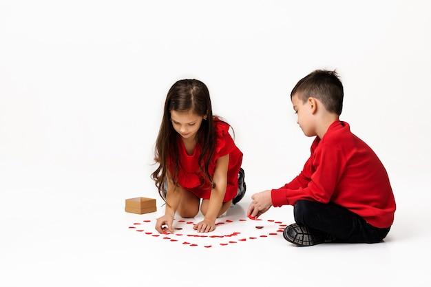 Gelukkig romantisch klein paarmeisje en jongen maken een grote hartvorm uit kleine papieren hartjes op de vloer