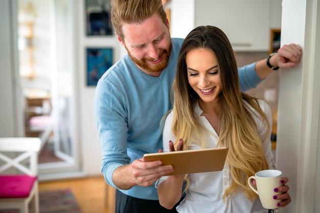 Gelukkig romantisch paar dat tablet gebruikt en thuis koffie drinkt