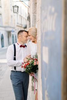 Gelukkig romantisch paar van middelbare leeftijd, knappe man in elegante kleding en mooie dame in witte jurk en boeket, poseren op zoek naar elkaar in de buurt van het vintage oude stadsgebouw