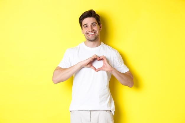 Gelukkig romantische man die hartteken toont, glimlacht en liefde uitdrukt, staande over gele achtergrond