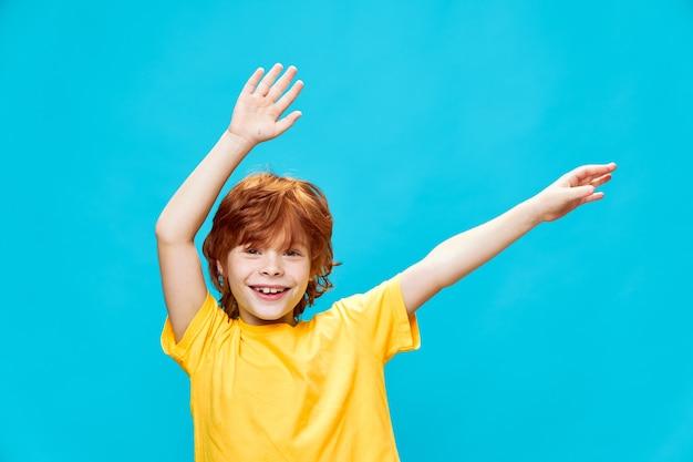 Gelukkig roodharig kind beweegt zijn handen naar de zijkanten op een blauw