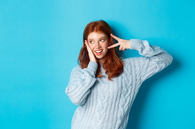 Gelukkig roodharig meisje lacht, toont vredesteken en kijkt naar links naar promo, staande in trui tegen blauwe achtergrond.