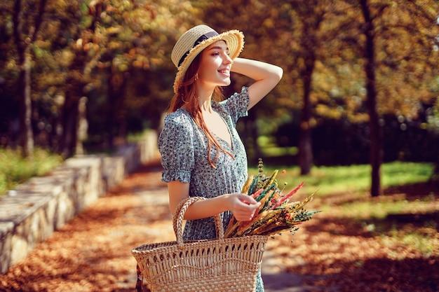 Gelukkig roodharig meisje loopt alleen in het herfstpark op een zonnige warme dag terwijl ze in de zomer een handtas vasthoudt