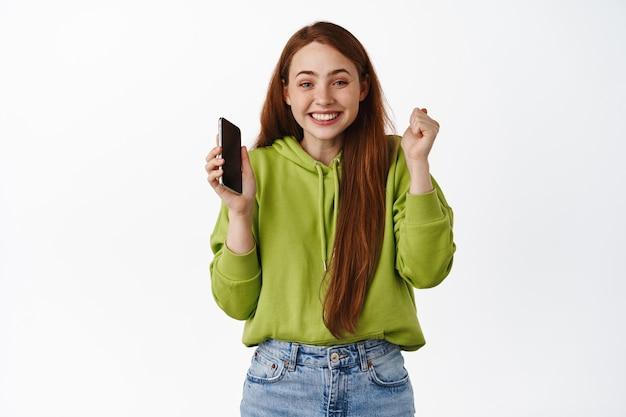 Gelukkig roodharig meisje verheugt zich, houdt smartphone vast en viert, wint op mobiele telefoon en triomfeert, koopt met korting, staat op wit