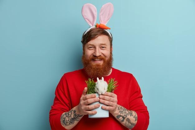 Gelukkig roodharige bebaarde blanke man in bunny oren houdt wit pasen konijn in kleine pot met vers groen gras, ziet er graag uit, geïsoleerd op blauwe muur. lente vakantie concept