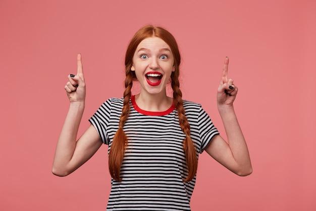 Gelukkig roodharige europese vrouw met gevlochten kapsel breed glimlachend, uiting van opwinding geïsoleerd, wijst met wijsvingers, toont product op plafond naar boven. promotie