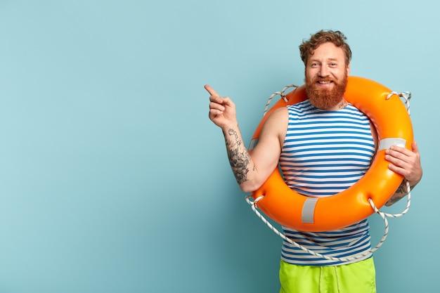 Gelukkig roodharige man met krullend haar, ontspant op zomerstrand, poseert met fel oranje reddingsboei