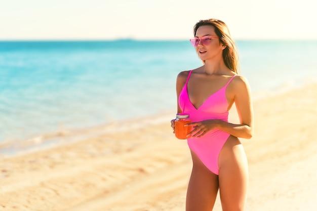 Gelukkig roodharige meisje in zonnebril en bikini tropisch zandstrand resort houdt drank vakantie