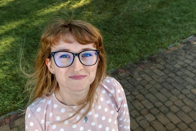 Gelukkig roodharige meisje met een bril die de camera van onder naar boven bekijkt