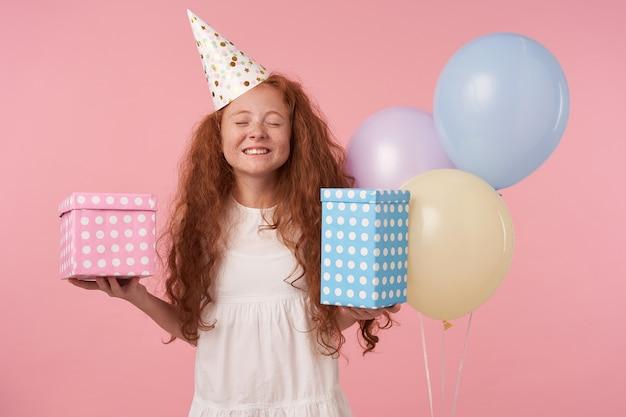 Gelukkig roodharige meisje met lang krullend haar in witte jurk en verjaardag pet viert vakantie, presenteert in handen met brede tevreden glimlach, geïsoleerd op roze studio achtergrond