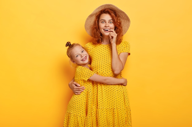 Gelukkig roodharige moeder en dochter poseren in soortgelijke jurken