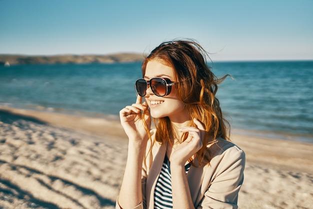 Gelukkig roodharige vrouw in beige jas en t-shirt op het zand in de buurt van de zee in de bergen