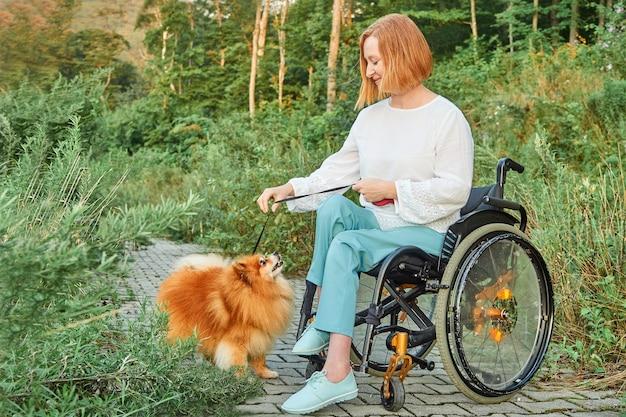 Gelukkig roodharige vrouw in een rolstoel voor een wandeling met haar hond, genietend van zonnig weer in de herfst.