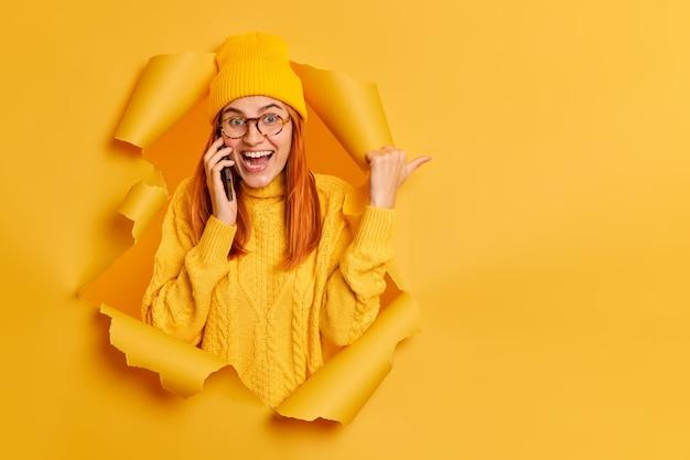 Gelukkig roodharige vrouw in hoed en trui breekt door papier gat heeft telefoongesprek, wijzend op kopie ruimte