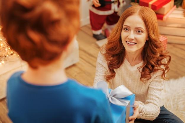 Gelukkig roodharige vrouw kijkt naar haar zoon met ogen vol liefde zittend op de vloer en geeft hem een prachtig ingepakt cadeau op een kerstochtend.