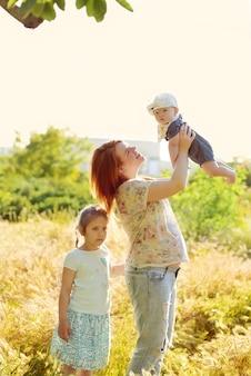 Gelukkig roodharige zwangere vrouw met twee kinderen buiten