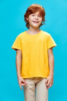 Gelukkig roodharigekind in geel t-shirt verbonden wijsvinger en duim en blauw