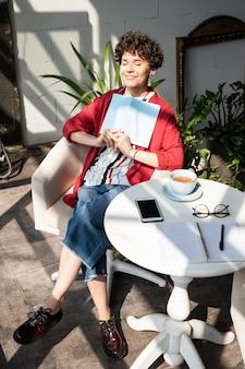 Gelukkig rustige jongedame met laptop zittend in een stoel door tafel in café, genieten van rust en thee