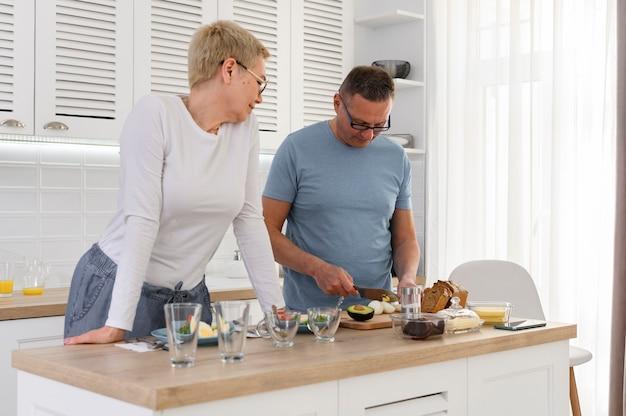 Gelukkig s paar dat van middelbare leeftijd gezond dieet plantaardig ontbijt samen voorbereidt