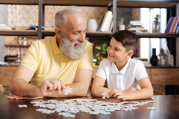 Gelukkig samen. aangename oudere man en zijn kleinzoon die stukjes van een legpuzzel vasthouden en breed glimlachend naar elkaar glimlachen