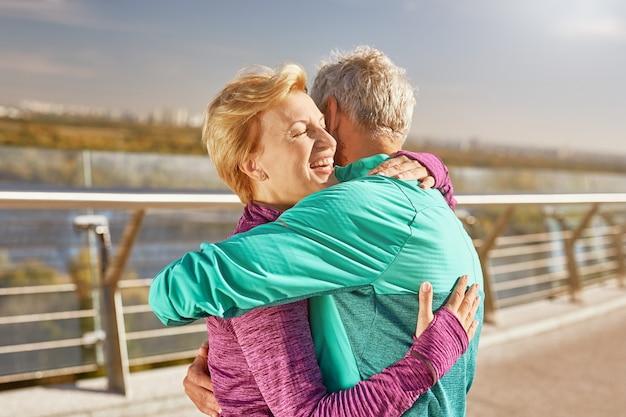 Gelukkig samen actief volwassen familiepaar in sportkleding omarmen na training in de stad