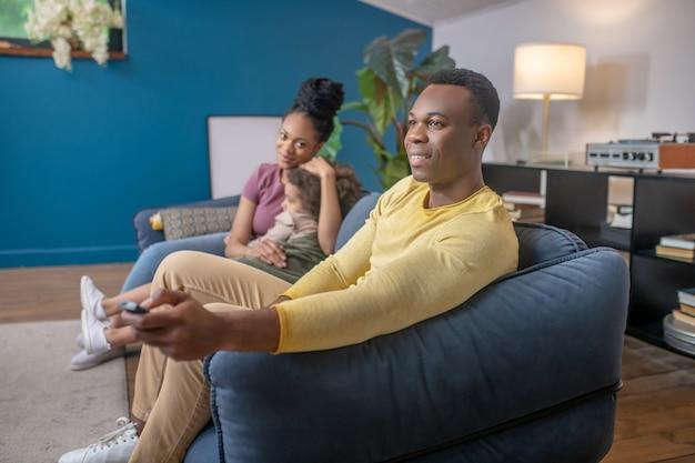 Gelukkig samen. donkerhuidige jonge volwassen echtgenoot, vrouw en dochter in vrijetijdskleding die gelukkig zit met rust op de bank thuis
