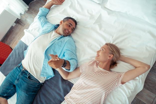 Gelukkig samen. man en vrouw liggend op een bed, hand in hand en kijken elkaar in de ogen, gelukkig ontspannend samen.