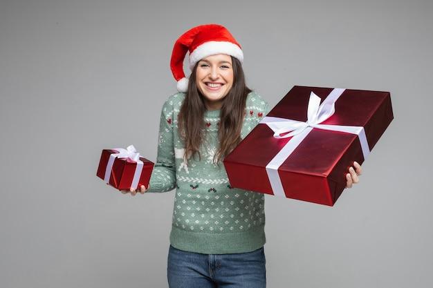Gelukkig santameisje in rode hoed en warme wintertrui met rode kerstmis nieuwjaarsgeschenken op grijze achtergrond