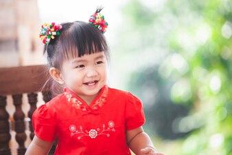 Gelukkig schattig Aziatische klein kind meisje in chinese traditie jurk glimlachen