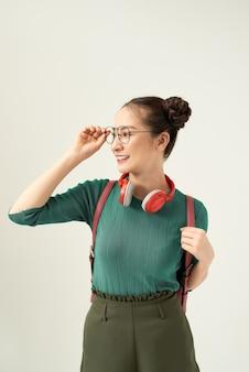 Gelukkig schattig jong studentenmeisje portret in glazen met rugzak op witte achtergrond