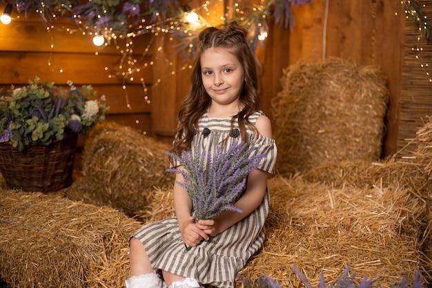 Gelukkig schattig klein meisje in boerderij met boeket van paarse bloemen