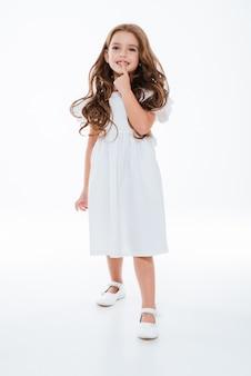 Gelukkig schattig klein meisje in jurk glimlachend en lopen