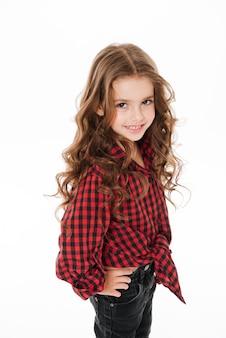 Gelukkig schattig klein meisje in plaid shirt staan en poseren