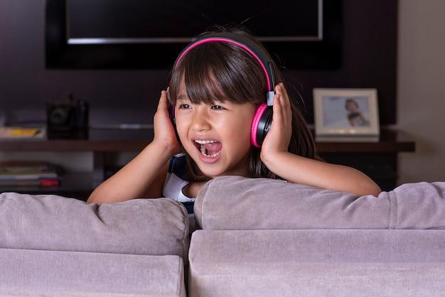 Gelukkig schattig klein meisje, luisteren naar muziek op de bank thuis