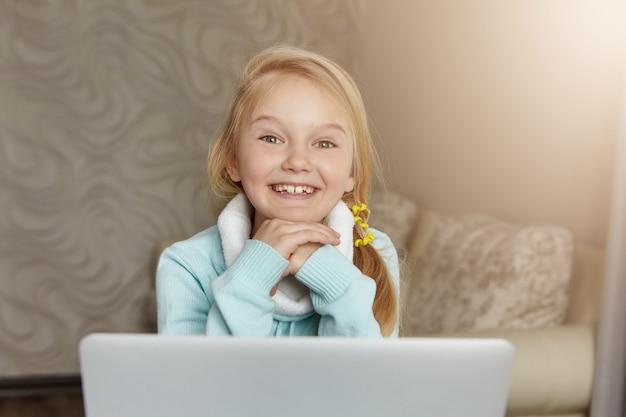 Gelukkig schattig klein meisje met slordige paardenstaart glimlachend gelukkig, gezicht op handen rusten