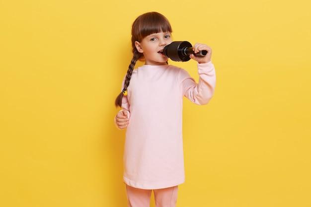 Gelukkig schattig klein meisje zingen lied op microfoon terwijl poseren geïsoleerd op gele achtergrond, donkerharige vrouwelijke chili met pigtails zingt in karaoke, camera kijken met opgewonden en blij blik.