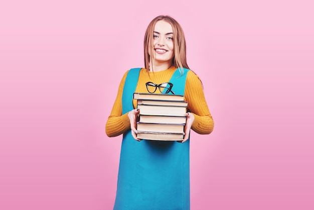 Gelukkig schattig meisje een stapel boeken in handen houden geïsoleerd op kleurrijke roze achtergrond.