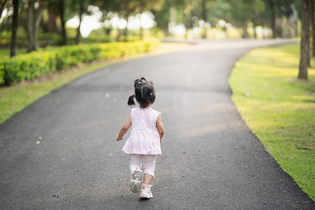 Gelukkig schattig meisje glimlachend en rennen in de tuin