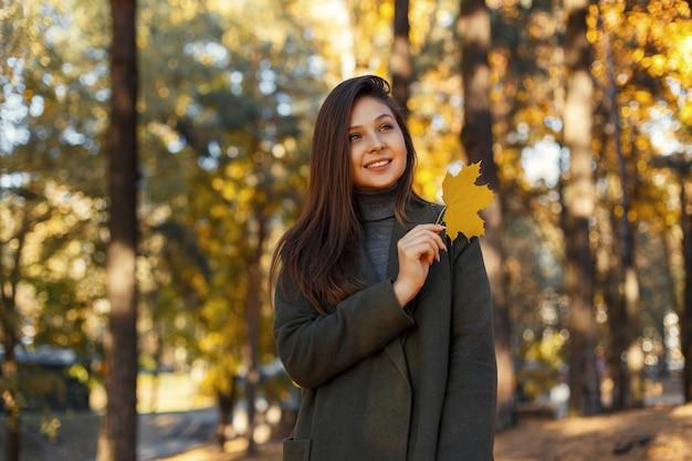 Gelukkig schattig meisje in een stijlvolle grijze jas loopt in een herfstpark met een geel blad in haar handen. aantrekkelijke vrouw.