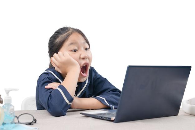 Gelukkig schattig meisje kijken naar video's streaming online op haar laptop thuis geïsoleerd op wit. homeschooling, leren op afstand en een nieuw normaal concept