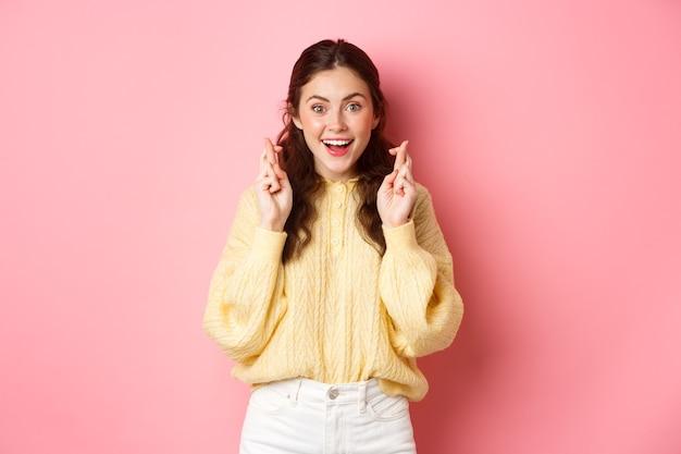 Gelukkig schattig meisje kruist vingers en glimlachende hoop op een droom die uitkomt, waardoor de examenresultaten van de wens wachten en hoopvol naar de camera kijken die over de roze muur staat