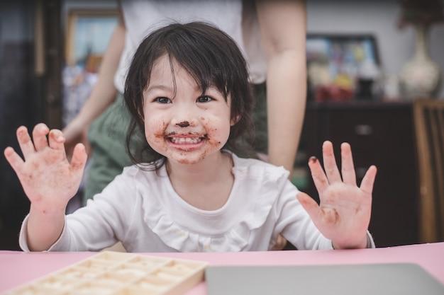 Gelukkig schattig meisje met een chocolade op haar gezicht.